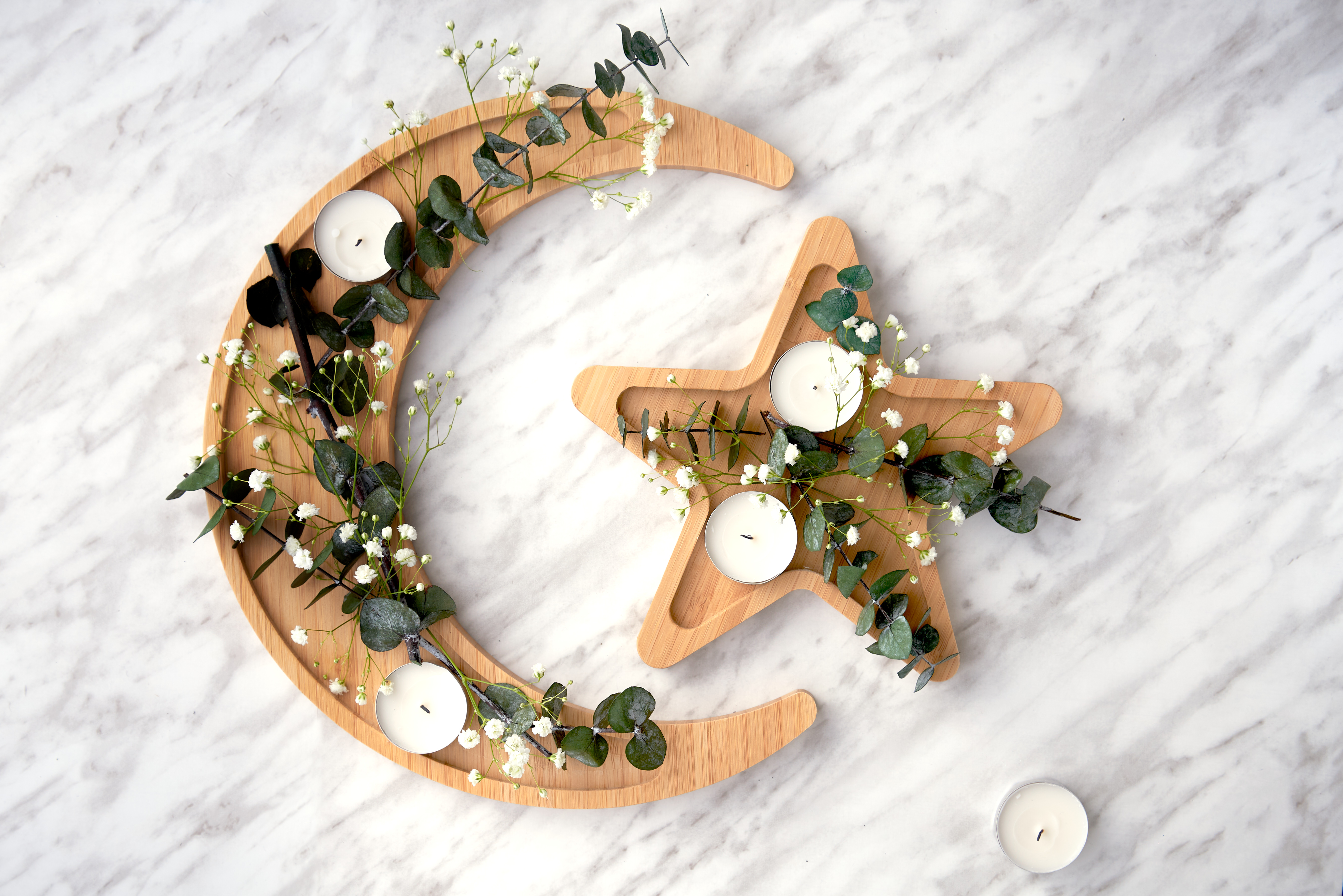 A moon and star bamboo wood platter with candles and green twigs rests on a white countertop