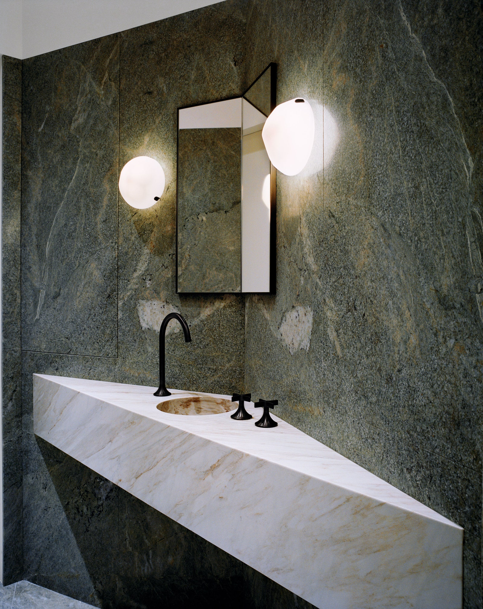 A green Zhivago marbleclad powder room in a Paris home redesigned by Pierre Yovanovitch.