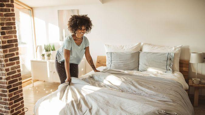Young woman making bed at home.