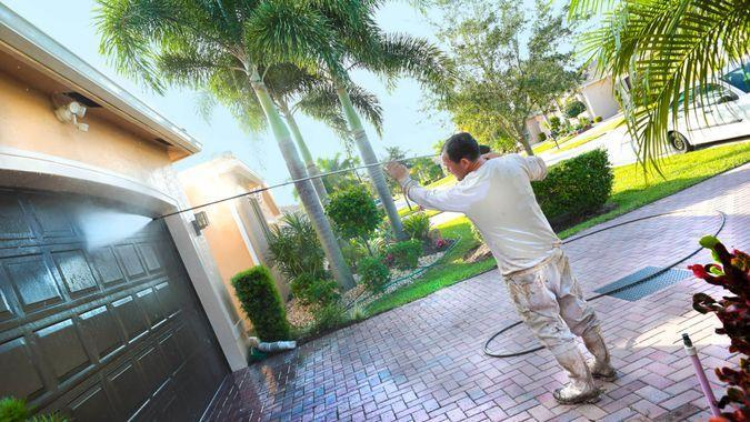 Hispanic male power washing an upscale home beore painting in a 55+ senior gated community.