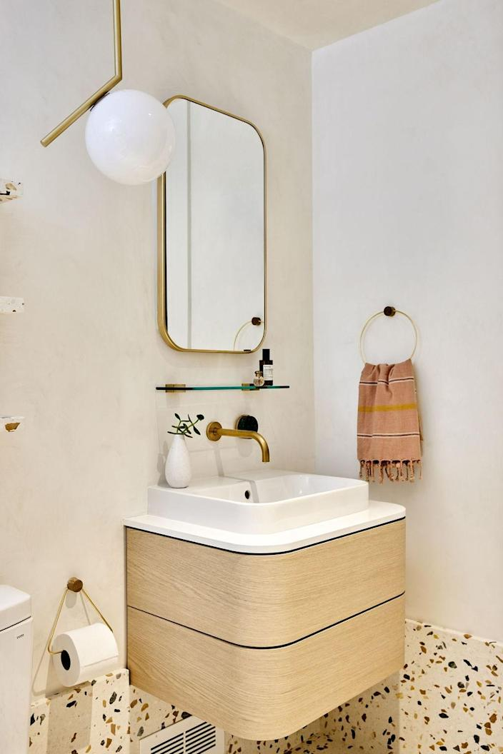 AFTER: The Italy-sourced terrazzo on the floor, the glass tiles from Fireclay, and warm brass fixtures in the shower that pick up on the base color of the terrazzo come together in a harmonious way.